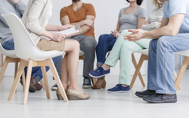 Support group talking in a circle, sitting on chairs
