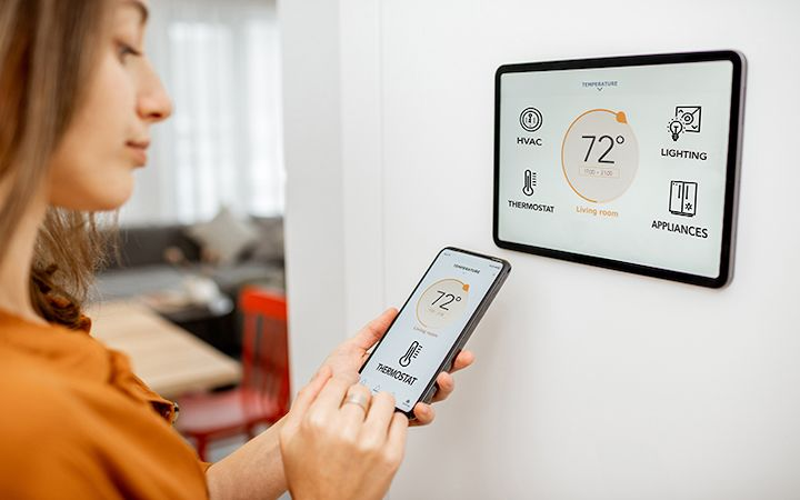Woman using smart home device on her wall and matching to her cell phone
