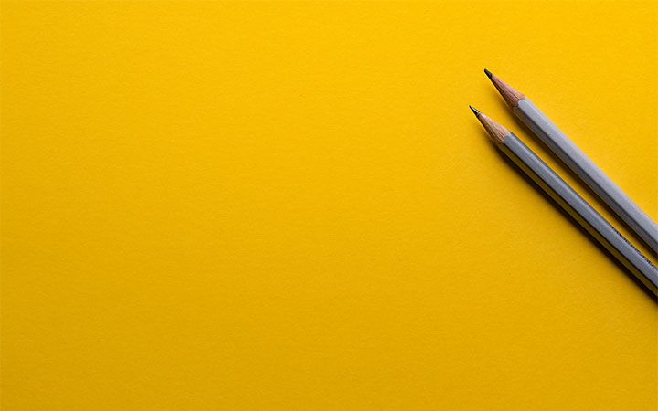 Two pencils with plain yellow background behind them