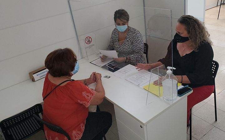 People meeting with a case manager from behind plexiglass divider