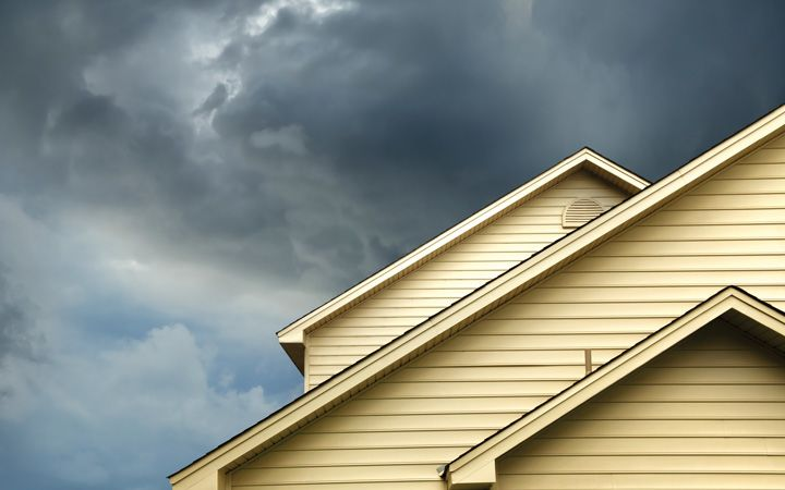 Top of a single family home with storm clouds above it
