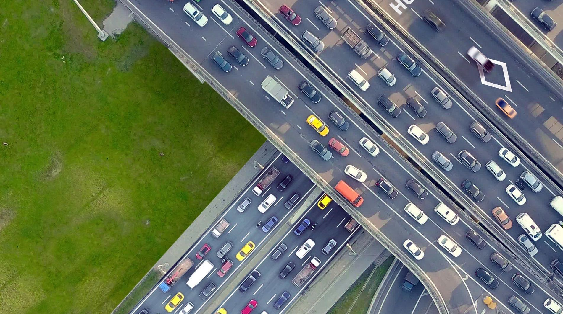 Birdseye view of roads with cars in traffic, on the ground road and overpass above it